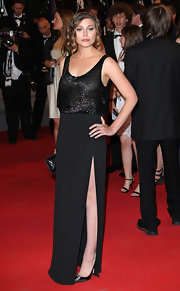 The daring slit in Elizabeth Olsen's black gown revealed elegant black satin pumps.