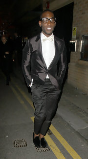 Tini Tempah opted for a classic black suit with a hint of sheen for his evening look while at an after party in London.