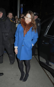 Emilia Clarke bundled up in a bright blue wool coat with classic fur trim.
