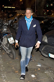 Lap Elkann dressed up jeans with a blue and white striped blazer and bright blue scarf.