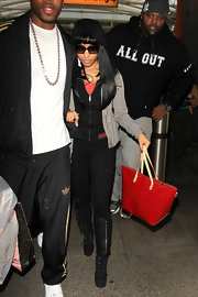 Nicki Minaj spiced up her travel attire with a red patent leather tote with tan leather straps.