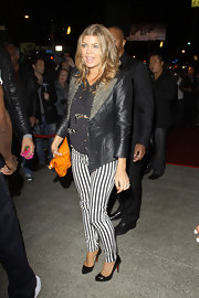 Fergie wears a black leather jacket with a studded lapel to attend a Hollywood event.
