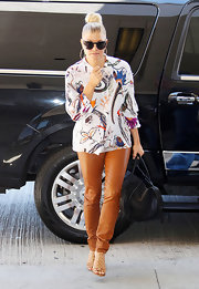 Fergie traveled in style in a colorful print blouse, leather pants and gold-ringed sandals.
