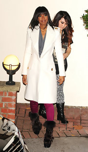 Kelly Rowland kept warm in a chic white coat paired with brown fur platform boots.
