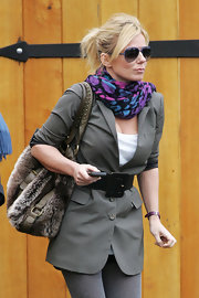 Geri wears a colorful 80's leopard print scarf with a neutral toned blazer and oversized belt.