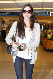 Genesis Rodriguez layered a woven cardi over her pastel stripes for a casually feminine travel look.