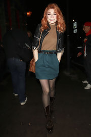 Nicola wears an adorable pocketed dark teal skirt belted and paired with a mini leather jacket.