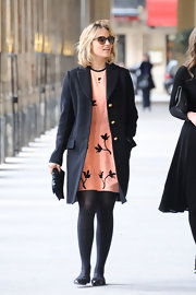 Dianna Agron winterized her feminine peach floral dress with a black pea coat and matching tights.
