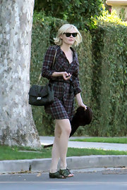 Kirsten Dunst maintains her signature indie style in lace up strappy sandals. Her favorite Ray-Ban's complete the look.
