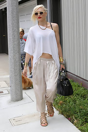 Gwen showed off her toned arms with this sheer, loose one-shouldered blouse that featured an asymmetrical hem.