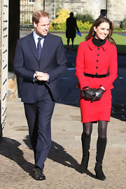 Kate Middleton teamed her sophisticated skirt suit with a black leather clutch, which matched her ladylike gloves.