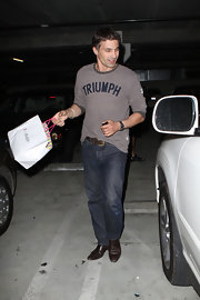 "Olivier looks casual yet cool in a brown t-shirt emblazoned with the word ""Triumph."""