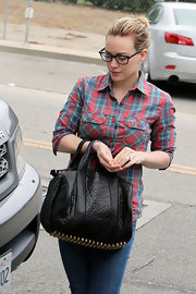 Hilary Duff strolled the streets in a laid back plaid shirt and leather studded duffel tote.