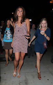 Hope Solo flaunted her bronze legs in a pink and black polka dot mini dress.