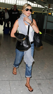 Jennifer Aniston traveled in style in London in a white tank, boyfriend jeans and a blue and white patterned scarf.