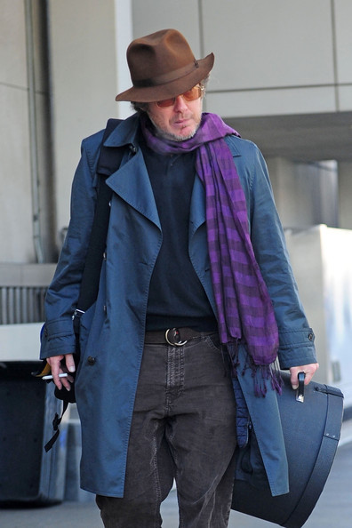 James Spader added some color to his travel look with this purple striped scarf.