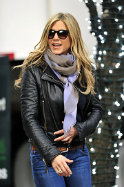 Jennifer plays it cool in a plaid scarf and a leather zip jacket.
