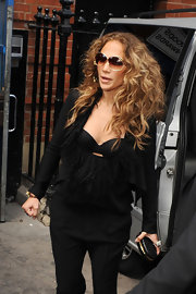 Jennifer Lopez teamed her all black attire with a matching python Jean-Jacques frame clutch.