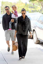 A very pregnant Jessica Alba was spotted out with her family toting a caramel Rock Stud leather shoulder bag. Embellished with silver pyramid studs, the bag features two shoulder straps and a flip lock fastening at at the front.