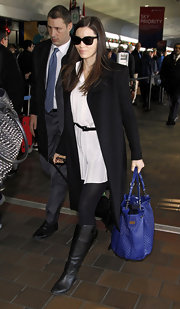 Jessica Biel traveled in style in a loose tunic paired with tights and black knee-high flat boots.