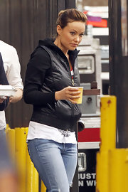 Olivia Wilde warmed up on set in a sporty black vest and a matching hoodie.