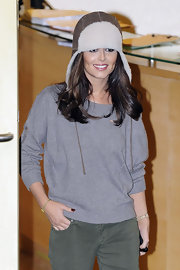 Cheryl dons a suede earflap hunting hat while leaving the Fountain Studios.