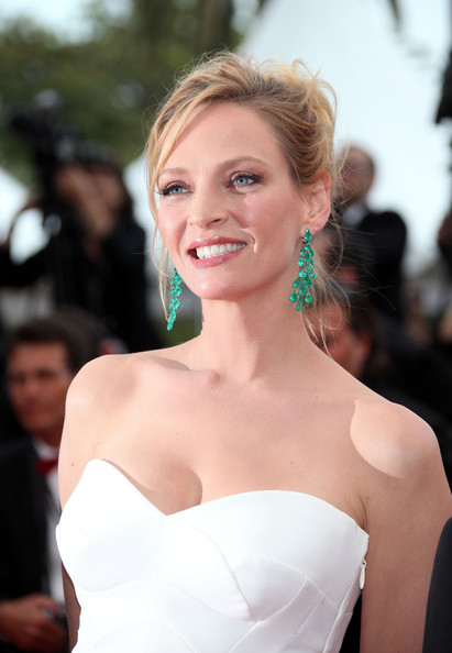 Uma Thurman gave her strapless white dress a boost of color with electrifying emerald green earrigns.