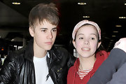 Justin shows off his recently shortened 'do at the Heathrow airport while posing with a fan.
