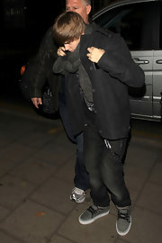 Justin wears a pair of gray canvas shoes with black laces and piping.