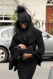 Naomi attended McQueen's funeral wearing this black brocade and feathered decorative hat. Her high fashion look was very suiting to mourn a fashion icon.