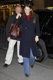 Kate Holmes kept her look classic with this basic navy coat, red sweater, and blue jeans.
