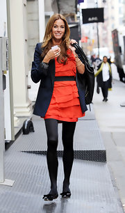 Kelly wears a long sleek blue blazer over a red dress while out in NYC.