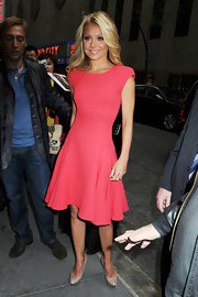 Kelly looked sweet as a peach in a coral sheath dress with a full skirt and padded shoulders.