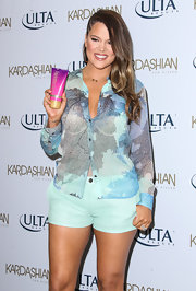 Khloe Kardashian matched mint-green short shorts with a sheer print blouse for a breezy look while promoting the new Kardashian Sun Kissed line.