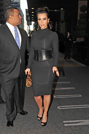 Kim dons a leather corset belt to accentuate her lovely curves.