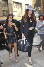 Khloe Kardashian teamed her streamlined look with a polished black tote back with white handles.
