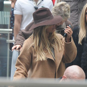 Kim Kardashian looked a little shy hiding under a brown walker hat as she arrived in London.