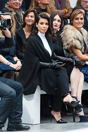 Kim looked elegant in a black draped cape and long leather gloves for her front row spot at the Stephane Rolland show.
