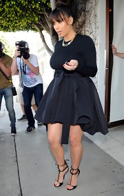 Kim Kardashian chose a fitted black blouse for her monochromatic look while leaving an LA hair salon.