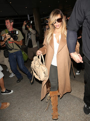 Kim Kardashian kept cozy with a pair of brown Taos suede boots and a bulky wool coat for a flight to LA.