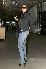 "Kim rocked a hot pair of ""Motorcycle Skinny Jeans"" in the ""Blue Exhaust"" wash. The detailed denim featured top-stitching on the knees and zips at the ankles and back pockets."