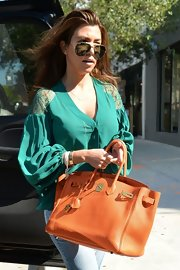 Kourtney's bright-orange tumbled leather tote gave her Miami look a fun Floridian feel.