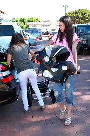 The budding model toted her nephew while sporting a bright pink top, jeans and metallic designer sandals.