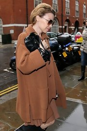 Kylie Minogue's black leather shoulder bag looked oh-so-tiny compared to her oversized neutral knit!