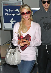 Paris Hilton added a pop of color to her look with an oversized pair of red plastic shades.