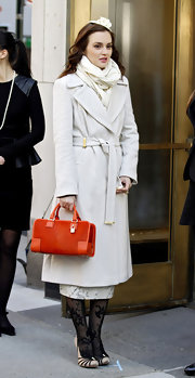 Leighton Meester got into character on the 'Gossip Girl' set adding as splash of color to her snow white style with an orange suede tote.