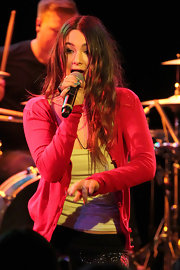 Fivel Stewart performed on stage wearing a tank top, a red cardigan, and a pair of beaded pants.