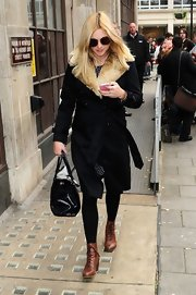 Fearne Cotton carried a classic black top-handle bowler bag with her fur jacket and brown lace-up boots.