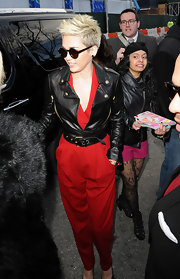 Miley Cyrus chose a black leather motorcycle jacket with gold zippers and attached belt for a somewhat edgy look while attending New York Fashion Week.