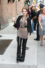 Miley posed for photos in an edgy pair of flared leather pants and mixed metal accessories.
